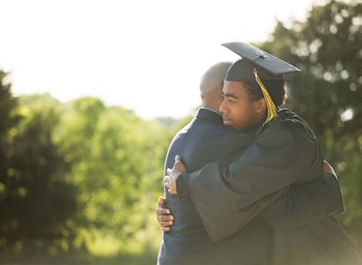 College graduate in cap and gown hugging dad