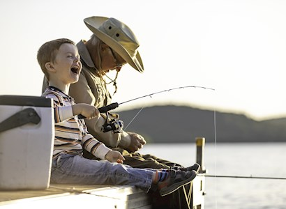 A grandfather fishes with grandson.