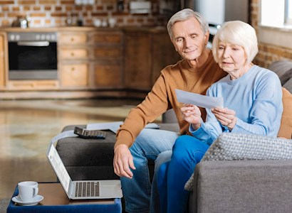 Older couple reading report on couch