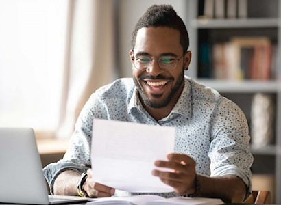 Young black man smiling while reading report