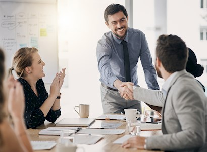 Co-workers shake hands at a meeting.